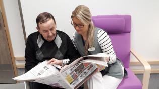 Sanomalehden lukua asukkaan kanssa Vuokkokodissa