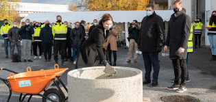 Kaupunginjohtaja Minna Arve muuraa Kirstinpuiston peruskiven.