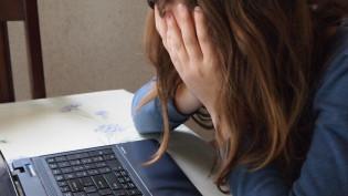 Opiskelija istuu tietokoneen ääressä kädet silmillä.