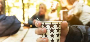 Nuoret juovat kahvia ulkona pahvikupista