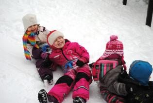 Neljä iloista lasta laskevat mäkeä jonossa talvihaalareissaan.