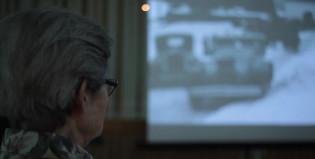 Harmaahiuksinen iäkäs nainen katsoo elokuvaa isolta kankaalta.
