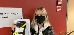 Taitaja2021-kilpailussa pronssia voittanut Emilie Manthe iloisena voittodiplomin ja kukkien kanssa.