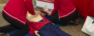 Kouluttajat opettavat elvytystä nuken avulla