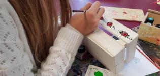 Nuori nainen maalaa puulaatikkoon ruusuja