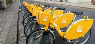 Keltaiset kaupunkipyörät pyöräasemalla rivissä