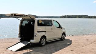 Kuljetusauto parkissa rannassa. Auton takaovi on auki ja ajoluiska laskettuna.
