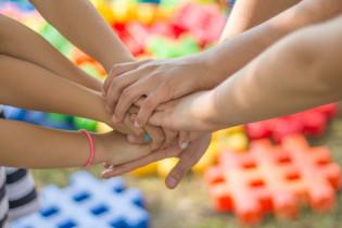 Kuvassa värikkäällä taustalla kolme käsiparia kurottaa yhteen
