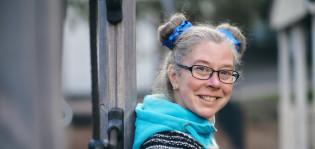 Kieli ja kulttuuriopettaja hymyilee päiväkodin pihalla