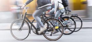 Kolme pyöräilijää kiitää tiellä vauhdikkaasti.