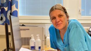 Naislääkäri istuu työpöytänsä ääressä.
