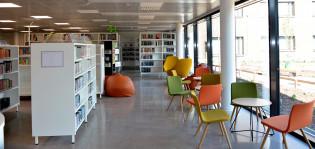 Hirvesalon kirjaston sisäkuva, kirjahyllyjä, värikäs tuolirymä, ikkuna antaa pihalle