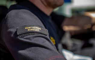 Kuvassa näkyy henkilön käsivarsi, jossa on Host Nation Support-tarra.