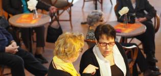 Kaksi naista etualalla keskustelemassa hyvinvointikeskuksessa