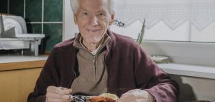 Iäkäs mies istuu keittiössä ruokapöydän ääressä ja syö ruokaa.
