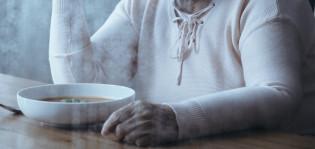 Iäkäs nainen istuu pöydän vieressä ja hänen edessään on lautasellinen keittoa.