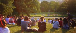 Ihmisiä istumassa nurmella auringonlaskun aikaan.