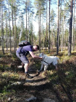 Nuori mies leikkii koiran kanssa metsässä.