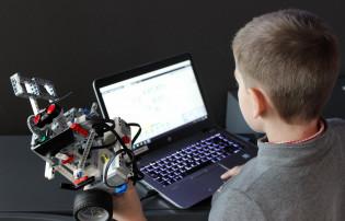 Poika katsoo tietokoneen ruutua. Vieressään hänellä on tekninen rakennelma.