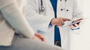 Lääkäri seisoo potilaan edessä ja selaa tablehhtia.