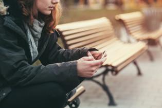 Nainen istuu penkillä puhelin kädessä