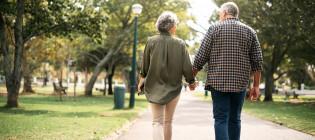 Iäkkäämmät nainen ja mies kävelevät käsi kädessä puistossa poispäin kamerasta