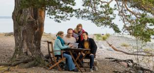 Kaksi naista ja miestä istuvan tietokoneen äärellä merenrannalla ja pohtivat asioita yhdessä.
