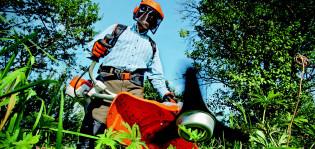 Mies käyttää kesällä ryteikössä raivaussahaa tai ruohoraivuria.