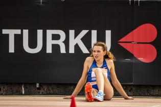 Urheilija Ella Junnila istuu tarkkaavaisen näköisenä maassa. Hänen takanaan seinässä on mustalla taustalla Kiss my Turku -logo.
