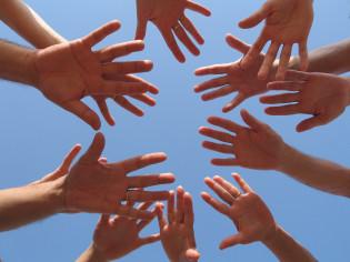 Käsiä ilmassa taivasta vasten muodostaen ringin