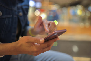 Henkilön kädessä on matkapuhelin.