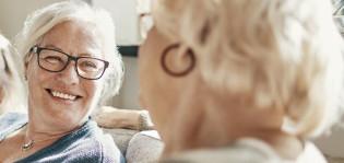Kaksi iäkkäämpää naista istuu sohvalla vierekkäin ja katsovat toisiinsa hymyillen.