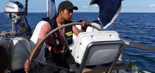Kuvassa lukiolainen purjestimassa Itämerellä. Lukiolaispoika on veneen ruorissa. Merellä tulee hiukan, mutta taivas on sininen ja purjehtijalla päällä vain rosan värinen t-paita ja musta lippalakki.