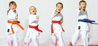 Kolme pikkutyttöä ja pikkupoika harrastamassa taekwondoa