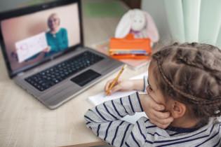 Lapsi käy koulua kotona tietokoneen ääressä.