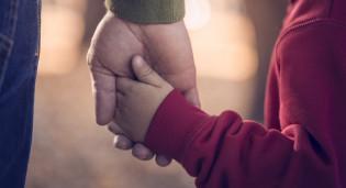 Lähikuvasssa aikuisen ja lapsen kädet, käsi kädessä