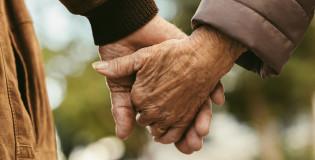 Iäkkään pariskunnan kädet kuvattuna käsi kädessä.