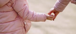 Lapsi ja aikuinen käsi kädessä