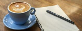 Kuvassa kahvikuppi, kynä ja lehtiö