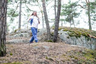 Nainen kävelee reippaasti kallioisessa metsässä.