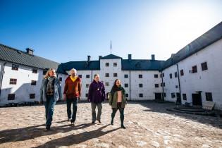 Neljä ihmistä kävelee Turun linnan sisäpihalla.