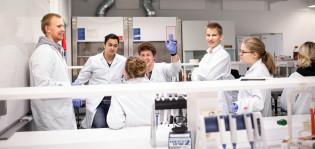 Seitsemän opiskelijan ryhmä biokemiallisessa tutkimuslaboratoriossa, yksi viittaa.