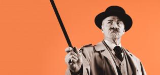 Mustavalkoinen Komisario Palmu oranssilla taustalla, kävelykeppi ojossa.