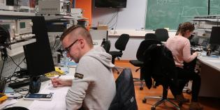 Tutkijoita istumassa työpöytien äärellä.