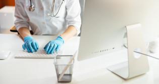 korona lääkäri tietokoneella kumihanskat kädessä