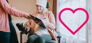 Pyörätuolissa istuva nainen katsoo ojennettua tablettia