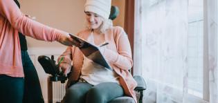 Pyörätuolissa istuva nainen katsoo ojennettua tablettia.