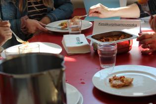 """Kuvassa kouluruokaraati testaa ruokia. Pöydässä on kattila, lautasia ja vuoka, jossa lukee """"kasvismoussaka""""."""