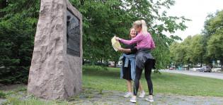 Kaksi ihmistä katsovat karttaa patsaan luona.