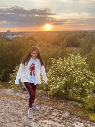 Nuori nainen kalliolla auringonlaskun aikaan